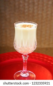 Eggnog. Christmas Eggnog with Cinnamon on a Shiny Red Plate. Eggnog is a traditional Christmas Drink. Food and Drink.