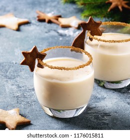 Eggnog Christmas milk cocktail with cinnamon, served in two glasses with shortbread star shape sugar cookies different size, decor toys, fir branch over blue texture background. Square image