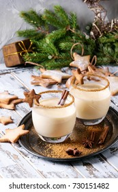 Eggnog Christmas milk cocktail with cinnamon, served in two glasses on vintage tray with shortbread star shape sugar cookies, decor toys, fir branch over white wooden plank table.