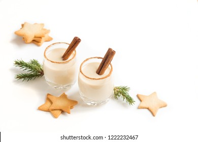 Eggnog with cinnamon and nutmeg for Christmas and winter holidays. Christmas Eggnog, gingerbread cookies isolated on white background.