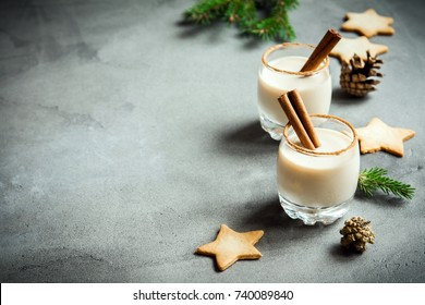 Eggnog with cinnamon and nutmeg for Christmas and winter holidays. Grey concrete background with Christmas Eggnog, gingerbread cookies, pine cones, copy space.