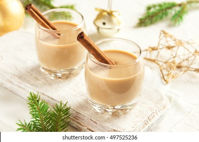 Eggnog with cinnamon sticks, Christmas decoration and ornaments over white background - homemade festive Christmas alcoholic drink, cocktail