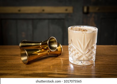 Eggnog cocktail with gold jiggers