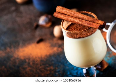 Eggnog cocktail hot winter or autumn drink with milk, eggs and dark rum, sprinkled with cinnamon and nutmeg in shot glass on blue dark background, copy space