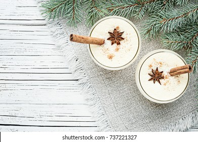 eggnog cocktail in two glasses arranged with christmas decoration on white wooden table