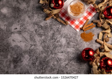 Eggnog shot from above with a Christmas / holiday decorated background with red glass ornaments and a string of pine cones, wood, and yarn with a pile of ground cinnamon sticks on a concrete surface.
