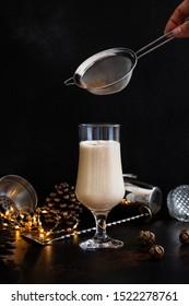 Eggnog traditional Christmas alcoholic drink with cinnamon and nutmeg. Hand sprinkled cinnamon powder on drink. Winter holidays mood. Christmas decorations.