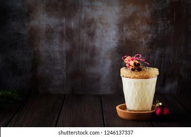 Eggnog Traditional Christmas drink milkshake with cinnamon on dark old background. Selective focus.