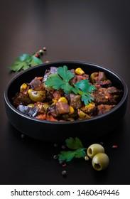 Eggplant caponata sauce in dark plate, dark background, isolated