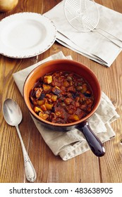 eggplant caponata, traditional sicilian dish. Served in a classic ceramic pan over a napkin on an aged wooden table. Surrounded by a silver spoon and a dish