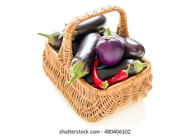 Eggplant and chili peppers in a basket on a white background.