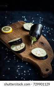 Eggplant and lemon slices cut on a wooden board, dark and moody food