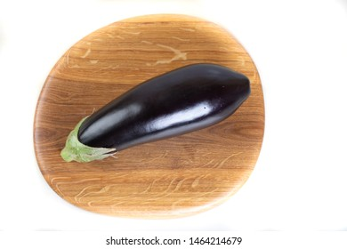 Eggplant on wooden board on white
