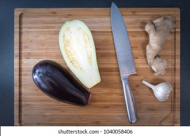 eggplant on wooden cutting board with knife, garlic and ginger