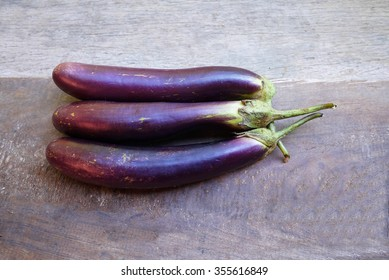Eggplant on wooden table .
