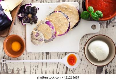 eggplant parmigiana ingredient over white rough table