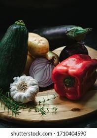 aubergine, poivrons, pommes de terre, ail, oignon et herbes sur planche en bois