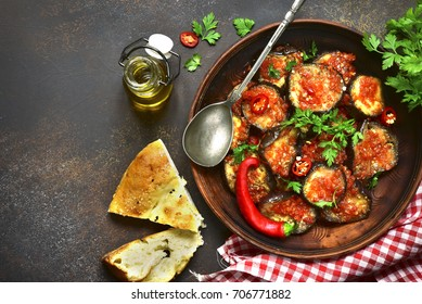 Eggplant slices in a spicy red sauce in a clay bowl over dark slate,stone or concrete background.Top view.