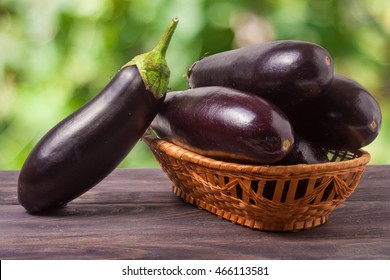 eggplant in a wicker basket on wooden table with blurred green background