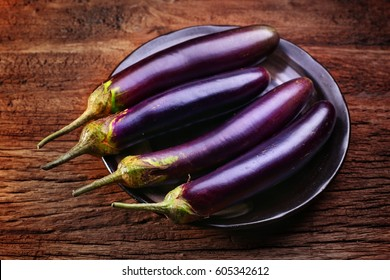 Eggplants, fresh organic eggplants on plate, put on rustic wooden. Selective focus and free space for text.