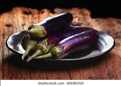 Eggplants, fresh organic eggplants on plate, put on rustic wooden, black background, Selective focus and free space for text.
