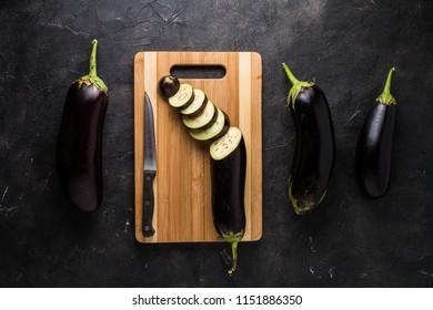 Eggplants on black textured background
