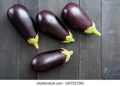 eggplants on black wood table background