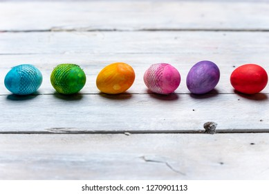 eggs in all the colors of the rainbow in a row on a bright, wooden background