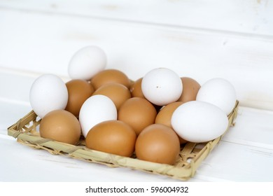 eggs in a basket on a white wooden background