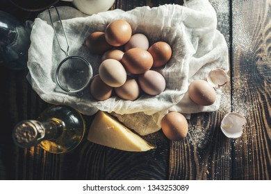 Eggs in a basket with scattered flour on a wooden table, top view