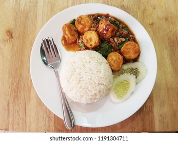 """Eggs bean curd fried stir with basil and pork in Thai style. Or in Thai is called as """"Pad Ka Paw Tao Hu Kai"""". Jasmine rice with cucumber also fork and spoon."""