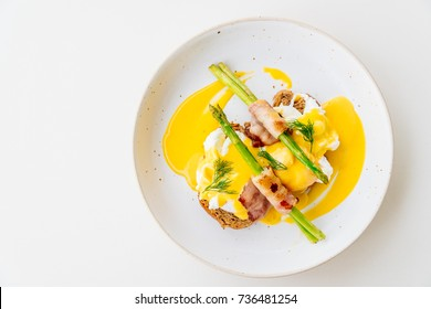 Eggs benedict with bacon twist asparagus in white plate