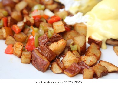 Eggs Benedict and Diced fried potato. Breakfast or Brunch Special with Cheese Sauce. Restaurant Food.