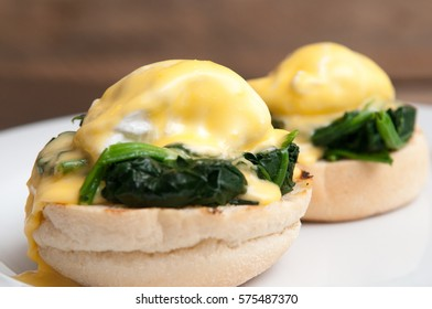 Eggs benedict or eggs florentine on a white plate in the cafe
