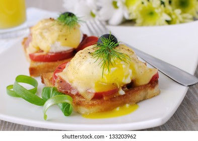 Eggs Benedict with ham and tomato on toast with cheese and orange juice