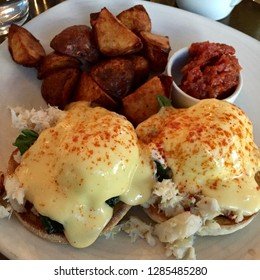 Eggs Benedict with hollandaise sauce and a side of potatoes.