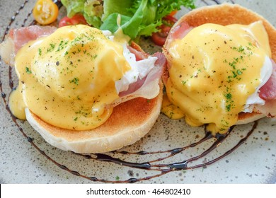 Eggs Benedict with little salad on the plate