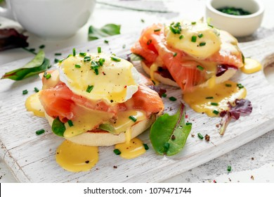 Eggs Benedict on english muffin with smoked salmon, lettuce salad mix and hollandaise sauce on white board