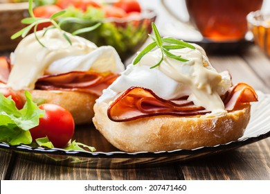 Eggs Benedict on toasted muffins with ham and sauce