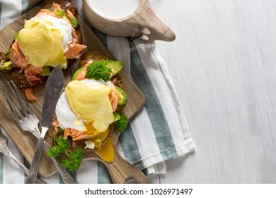 Eggs benedict, scandinavian style - with avocado and poached salmon. Top view. Copy space background.