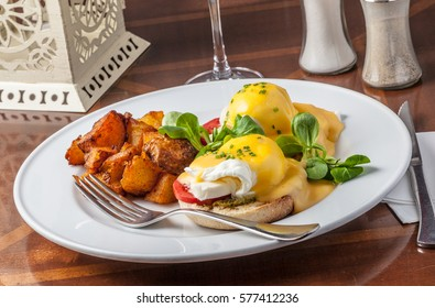 Eggs Benedict served with potatoes for brunch