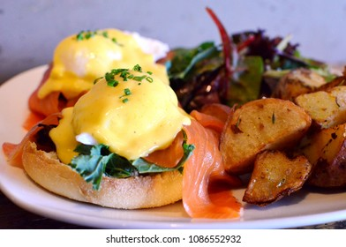 Eggs benedict with smoked salmon, served with salad and fries
