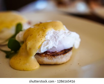 Eggs Benedict, a traditional American breakfast that consists of two halves of an English muffin topped with a poached egg, bacon or ham, and hollandaise sauce.