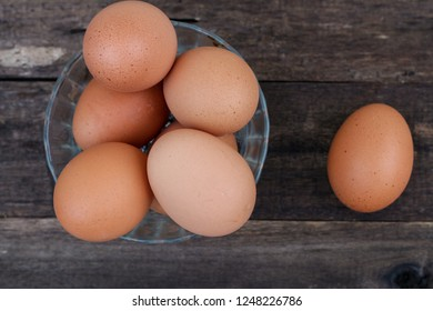 Eggs in the bowl over the wooden table