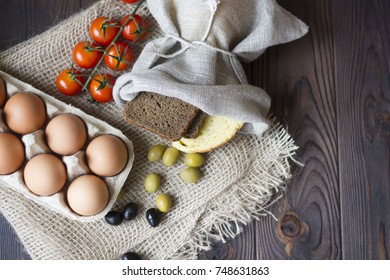 eggs, bread, olives,tomatoes and spices on a wooden table