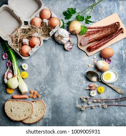 Eggs, bread, smoked sausage and vegetables. Easter food on grey, stone backround.