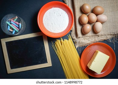 eggs, butter, pasta, flour and empty black board on sackcloth