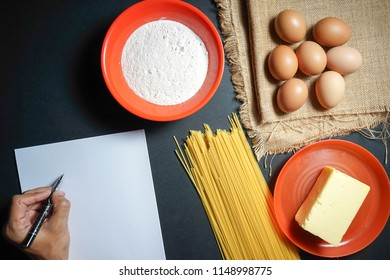 eggs, butter, pasta, flour and empty white paper on sackcloth