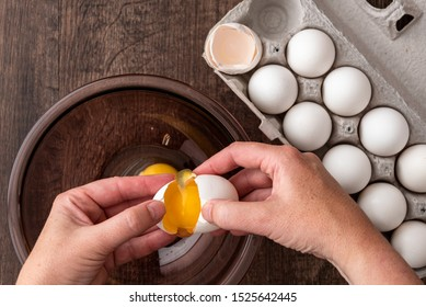 Eggs in cardboard egg carton, woman's hands opening egg into glass bowl, raw egg in bowl, on a wood table