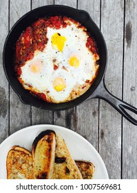eggs cooked in tomato sauce in cast iron pan